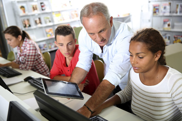 Teacher working looking at a computer screen with 2 students
