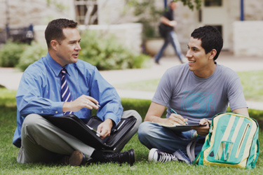Teacher and student having a conversation while sitting in the grass