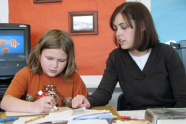 A mentor helping a student in a classroom