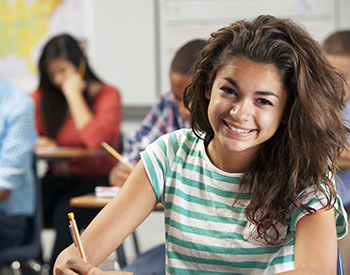 Smiling girl writing at desk