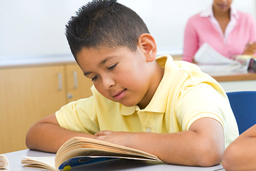 student reading a book in a classroom