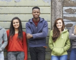 five high school students standing against a wall