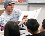 Photo of older student reading to children