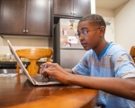 student sitting at his kitchen table using a computer