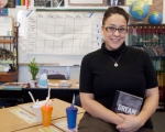 Teacher at her desk in a classroom looking forward holding a book