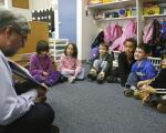A teacher reading a book to a group of kindergarteners