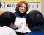 English Language Learners read book with female teacher