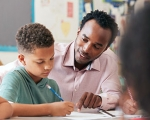 Photo of teacher assisting student with homework
