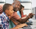 Photo of teacher and student at a computer