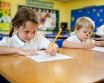 2 students writing at their desks in the classroom