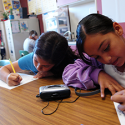 English Language Learners listen to audiobooks at a table