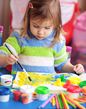 Female preschool student painting in the classroom