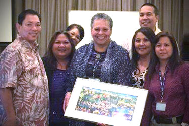 Yvonne Ryans holding a painting with other educators in Guam